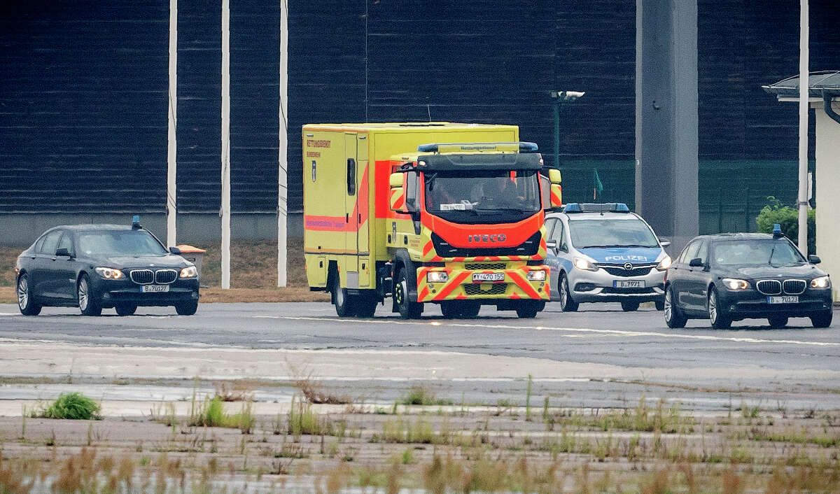 An ambulance which is believed to carry Kremlin critic Alexei Navalny leaves Tegel Airport in Berlin, Germany, Saturday, Aug.22, 2020. The Russian opposition member has been in a coma since Thursday and is on artificial respiration. ( Michael Kappeler/dpa via AP)