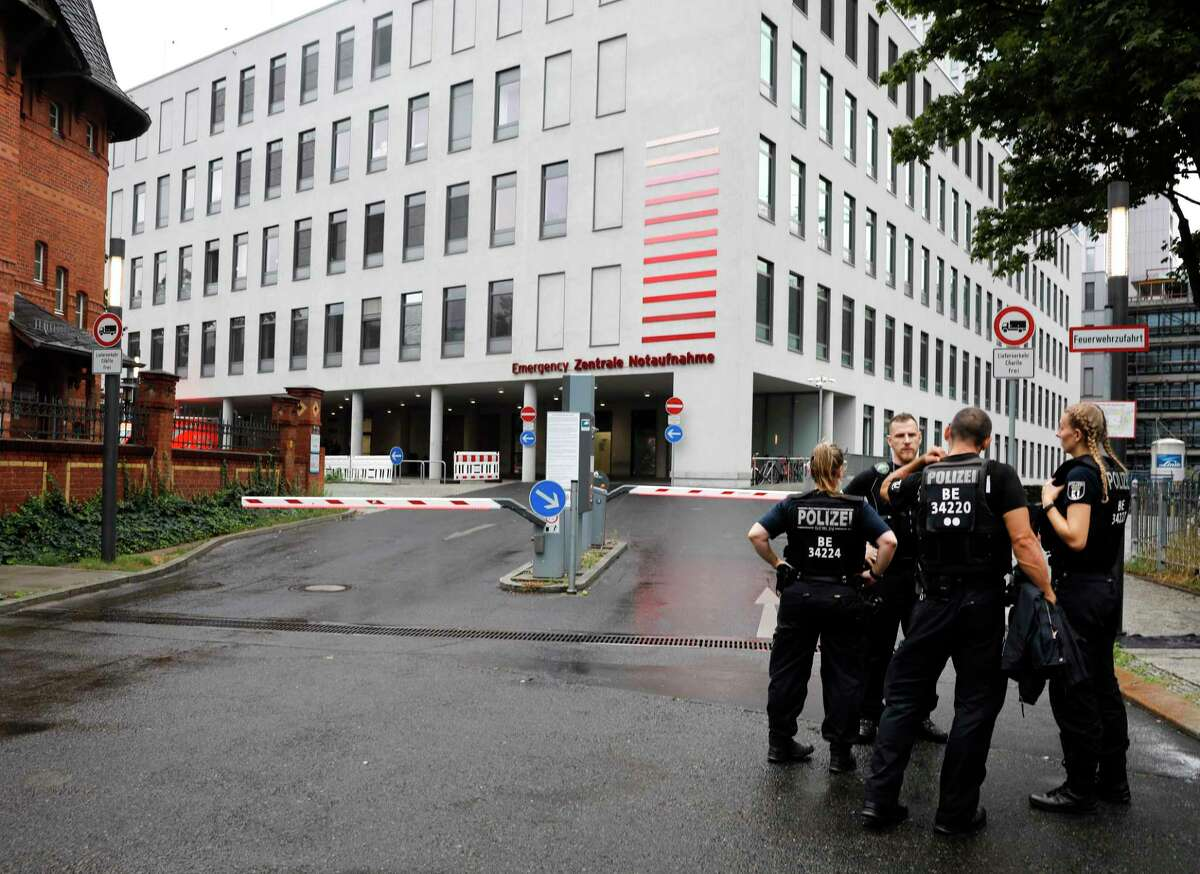 German police officers stand in front of the emergency entrance of the Charite hospital where Alexei Navalny is expected to arrive in Berlin, Germany, Saturday, Aug.22, 2020. The dissident who is in a coma after a suspected poisoning has been transferred from the Siberian city of Omsk. Navalny is flown to Germany to receive treatment. (AP Photo/Markus Schreiber)