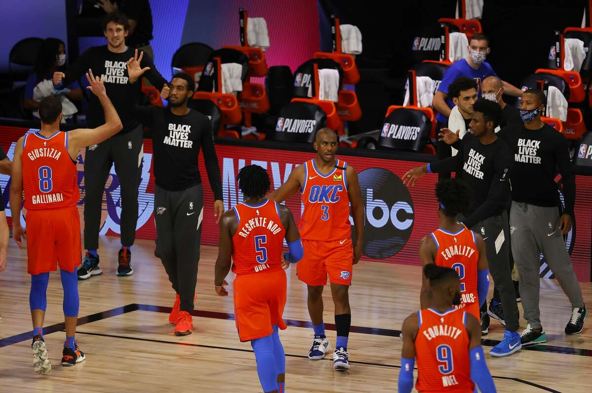 LAKE BUENA VISTA, FLORIDA - AUGUST 22: Chris Paul #3 of the Oklahoma City Thunder is congratulated by teammates following the team's overtime win against the Oklahoma City Thunder in Game Three of the Western Conference First Round during the 2020 NBA Playoffs at The Field House at ESPN Wide World Of Sports Complex on August 22, 2020 in Lake Buena Vista, Florida. NOTE TO USER: User expressly acknowledges and agrees that, by downloading and or using this photograph, User is consenting to the terms and conditions of the Getty Images License Agreement. (Photo by Mike Ehrmann/Getty Images)
