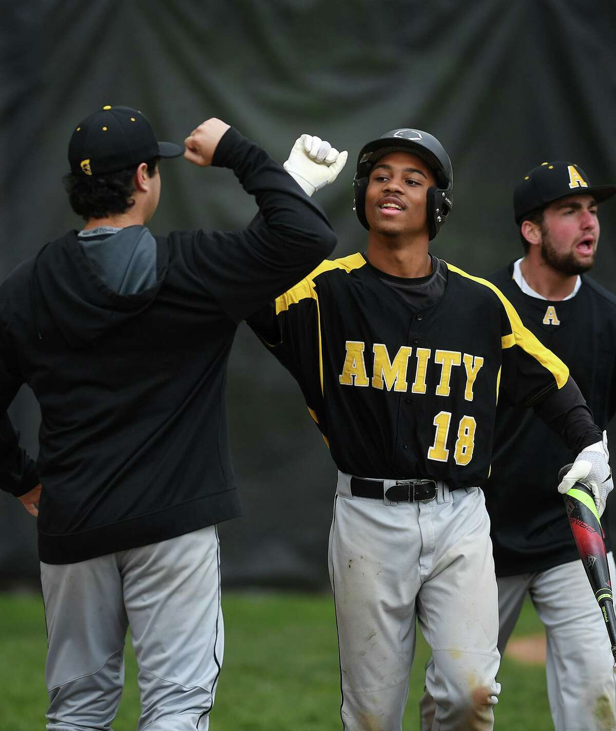 """Amity's Julian """"Juju"""" Stevens high fives a teammate after scoring a run against Hand in May, 2019."""