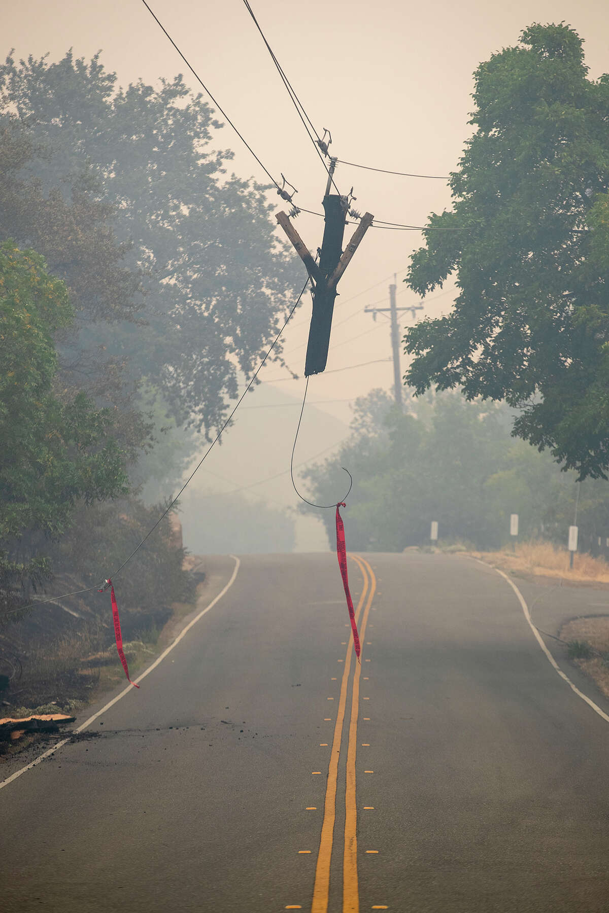 A utility pole damaged by the LNU Lightning Complex wildfire hangs over Gibson Canyon Road in Vacaville, Calif., on Thursday, Aug. 20, 2020. (Photo by Anda Chu/MediaNews Group/East Bay Times via Getty Images)