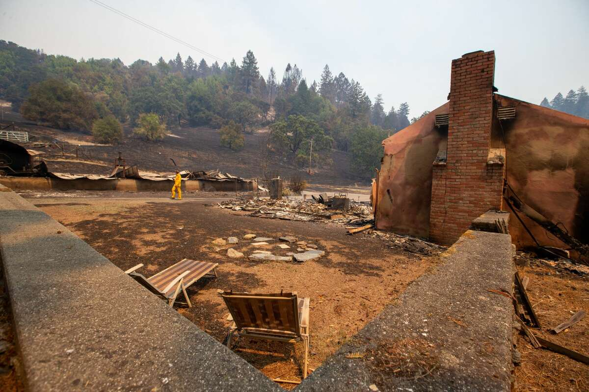 A reporter walks past the remains of a house destroyed by the LNU Lightning Complex fire on Wallace Creek Road in Healdsburg, Calif., on Friday, Aug., 21, 2020. (Photo by Ray Chavez/MediaNews Group/East Bay Times via Getty Images)