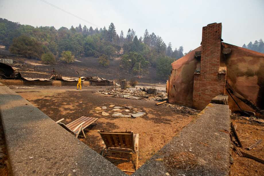 A reporter walks past the remains of a house destroyed by the LNU Lightning Complex fire on Wallace Creek Road in Healdsburg, Calif., on Friday, Aug., 21, 2020. (Photo by Ray Chavez/MediaNews Group/East Bay Times via Getty Images) Photo: MediaNews Group/East Bay Times V/MediaNews Group Via Getty Images / Bay Area News Group - Digital First Media