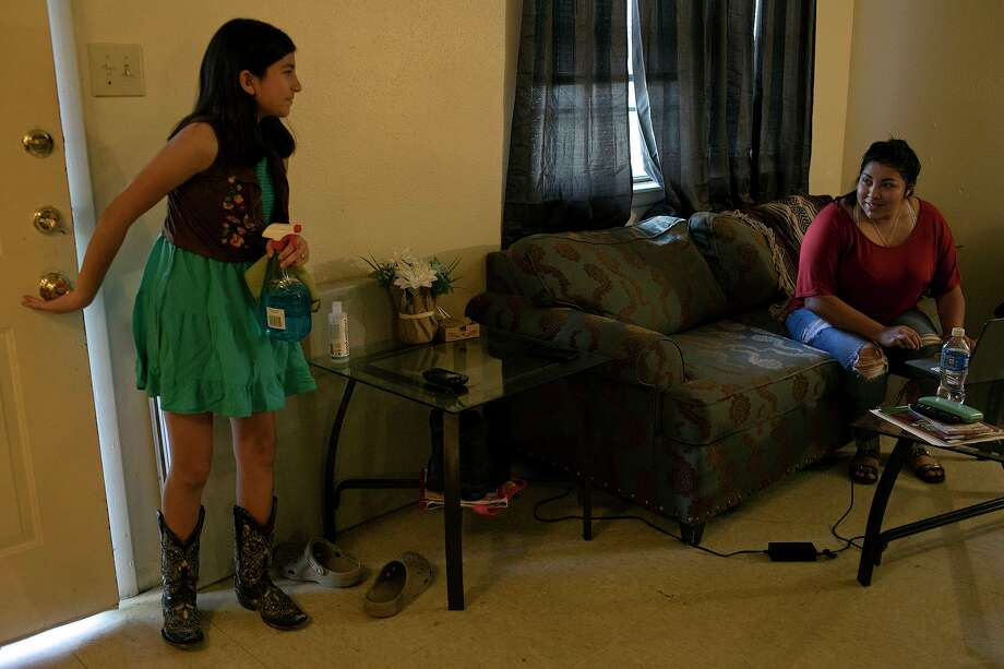 Elexia Herrera, 10, heads inside to clean her bedroom window after cleaning the outside as her mother, Zenaida Jeana Tijerina, sits inside their home in Poteet on Wednesday, Aug. 19, 2020. Jeana and her children all had COVID-19. Photo: Lisa Krantz /Staff Photographer / San Antonio Express-News