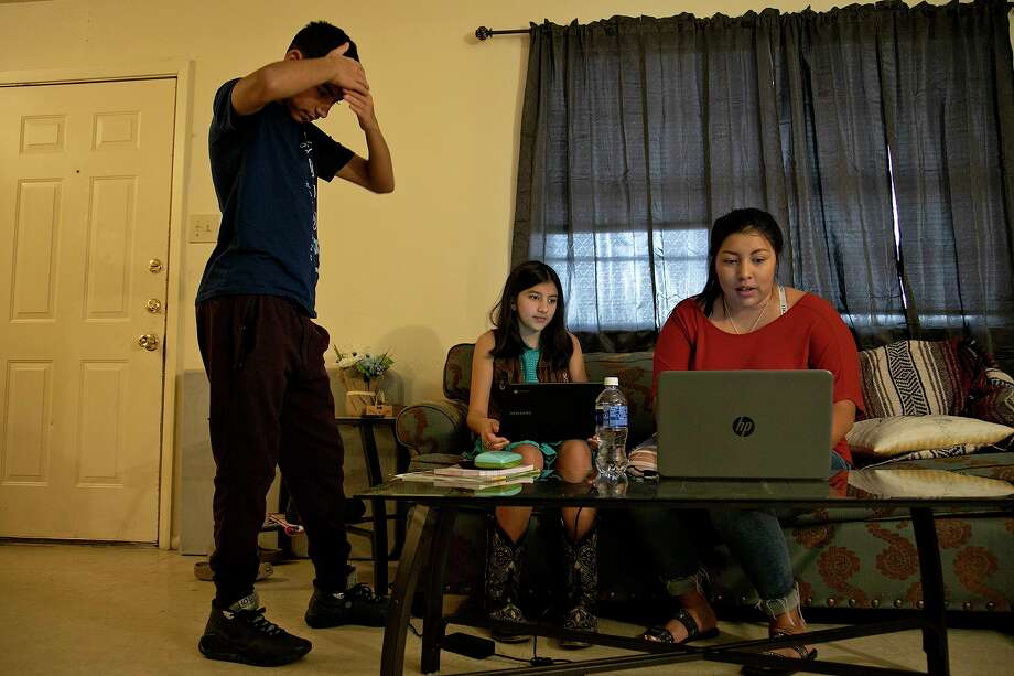 Gabriel Herrera, 12, stands by to help as his sister, Elexia Herrera, 10, and their mother, Zenaida Jeana Tijerina, try to log into the children's school email accounts to see their class schedules at their home in Poteet on Wednesday, Aug. 19, 2020. Jeana and her children all had COVID-19. Photo: Lisa Krantz /Staff Photographer / San Antonio Express-News