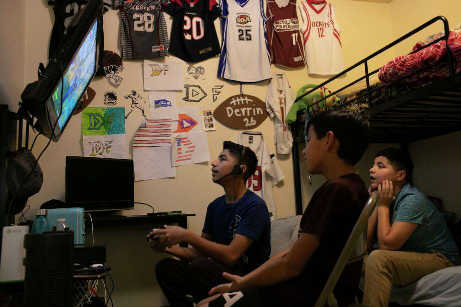 Gabriel Herrera, 12, from left, plays Fortnite as his brothers, Zerrik Herrera, 9, and Derrin Herrera, 11, watch at their home in Poteet on Wednesday, Aug. 19, 2020. The brothers all had COVID-19 with their sister and mother. Photo: Lisa Krantz /Staff Photographer / San Antonio Express-News