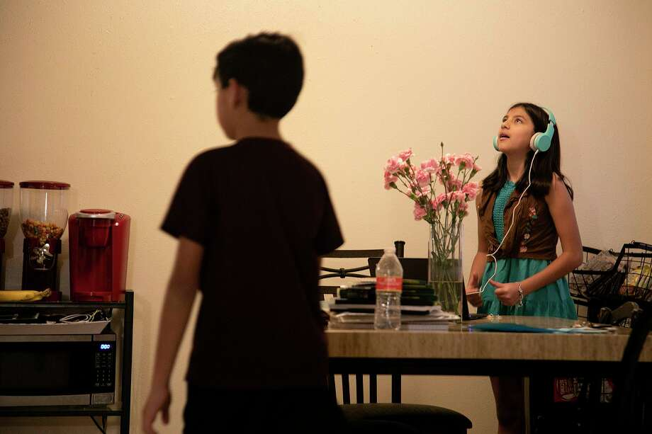 Elexia Herrera, 10, listens to music and practices TikTok dances as her brother, Zerrik Herrera, 9, walks to the kitchen for a snack at their home in Poteet on Wednesday, August 19, 2020. Alexia, her siblings and their mom have all recovered from COVID-19. Photo: Lisa Krantz, Staff / Staff Photographer / San Antonio Express-News