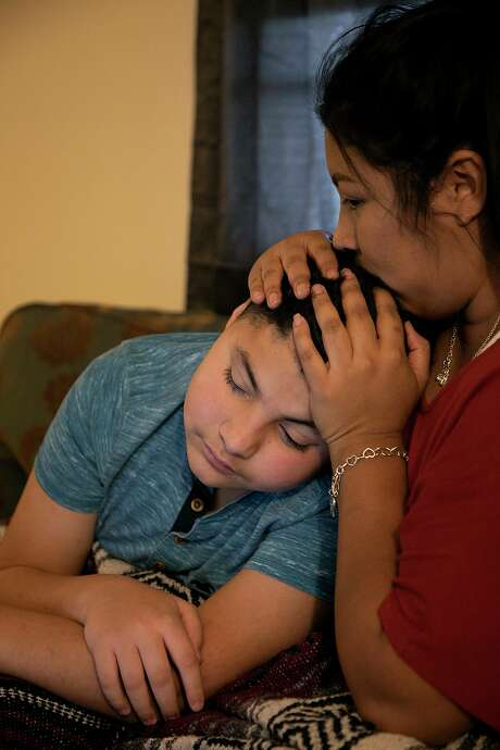 Zenaida Jeana Tijerina comforts her son, Derrin Herrera, 11, as they answer questions during an ADHD assessment for him over the phone at their home in Poteet on Wednesday, Aug. 19, 2020. Jeana and her children all had COVID-19. Photo: Lisa Krantz /Staff Photographer / San Antonio Express-News