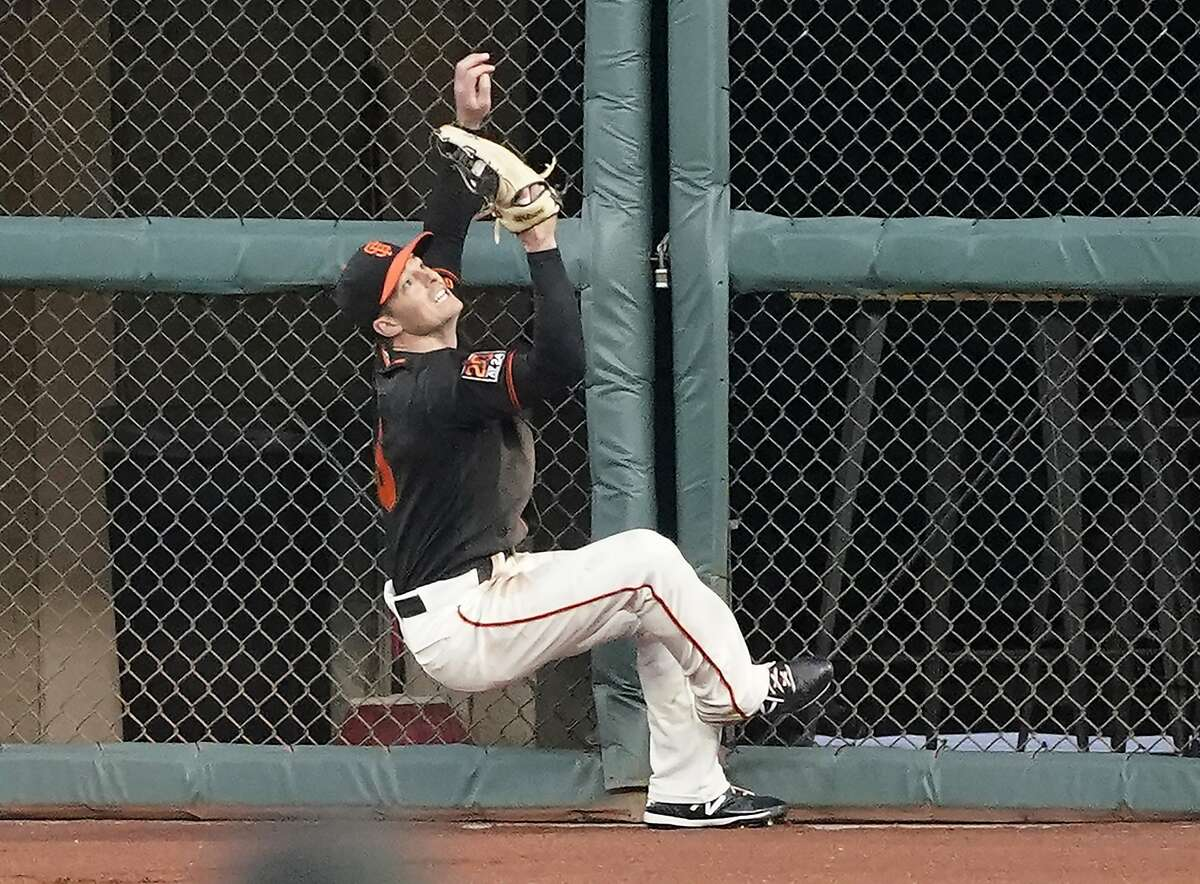 San Francisco Giants right fielder Mike Yastrzemski (5) makes a leaping catch against the fence on a hit by Arizona Diamondbacks' Ketel Marte during the sixth inning of a baseball game in San Francisco, Saturday, Aug. 22, 2020. (AP Photo/Tony Avelar)
