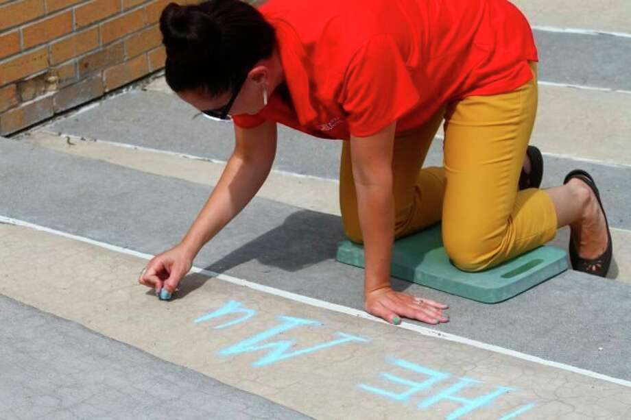 Maggie Walcott writes a welcoming message for students at the 2019 chalk the walk event. This year, the event will welcome students back after a long break while also raising awareness for racial injustice. (Pioneer file photo)
