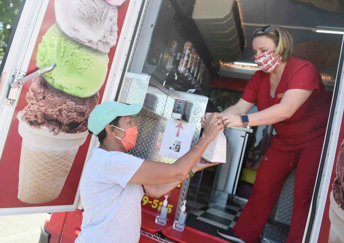 Stamford Senior Center Executive Director Christina Crain, left, takes ice cream from Ice Cream Emergency Shireen D'Andrea at the ice cream drive-thru for members of the Stamford Senior Center at the Jewish Community Center in Stamford, Conn. Thursday, Aug. 20, 2020. About 150 seniors picked up ice cream from the Ice Cream Emergency truck Thursday afternoon. The Senior Center will host a taco truck drive-thru next month.