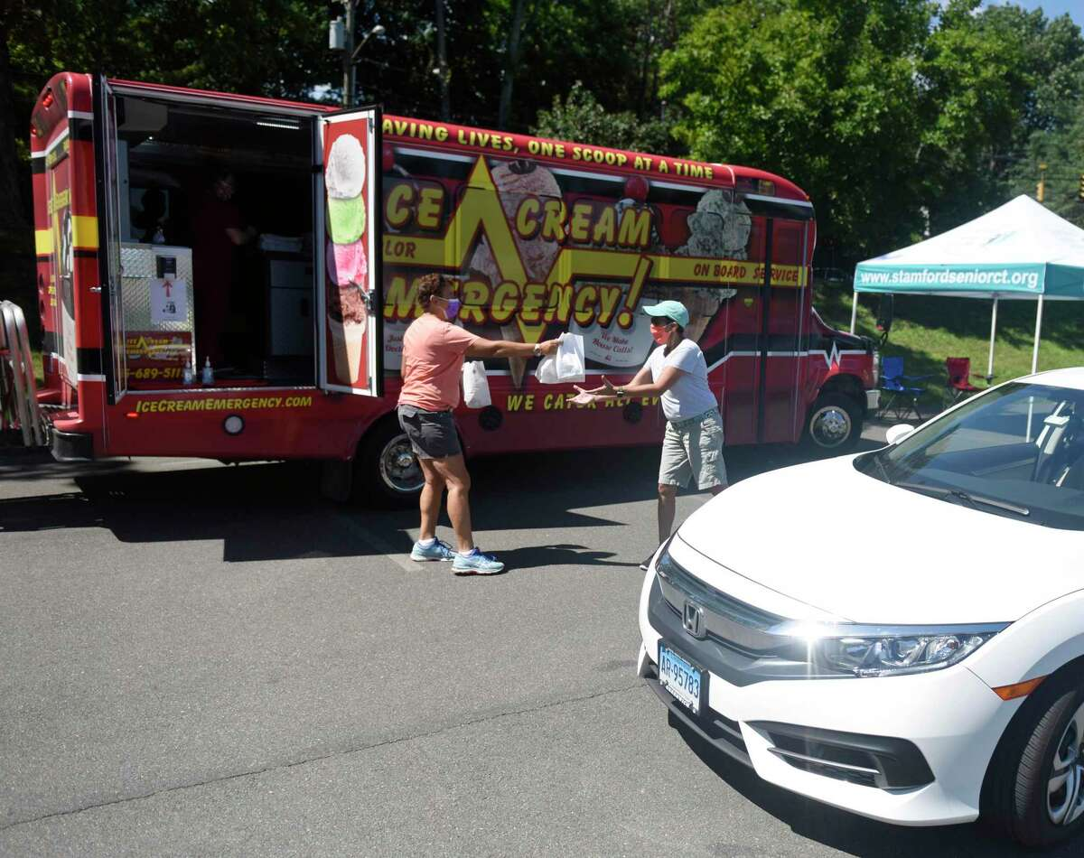 Volunteer Angela Spanakos, left, and Stamford Senior Center Executive Director Christina Crain distribute ice cream at the ice cream drive-thru for members of the Stamford Senior Center at the Jewish Community Center in Stamford, Conn. Thursday, Aug. 20, 2020. About 150 seniors picked up ice cream from the Ice Cream Emergency truck Thursday afternoon. The Senior Center will host a taco truck drive-thru next month.