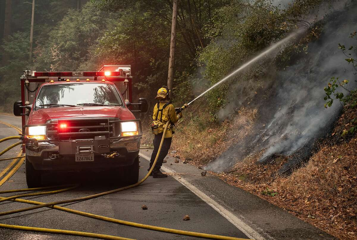 A firefighter sprays down the hillside at Highway 9 in Boulder Creek on Aug. 22, 2020. The CZU Lightning Complex Fire has so far been contained to one side of the highway and crews are monitoring the blaze to ensure it does not jump the road.