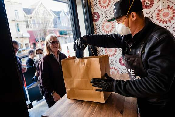 David Nayfield, co-owner of Che Fico Alimentari serves a takeaway meal to long time  customer Peggy Cling who is celebrating her 50th wedding anniversary in San Francisco, Calif. on Saturday, March 21, 2020.