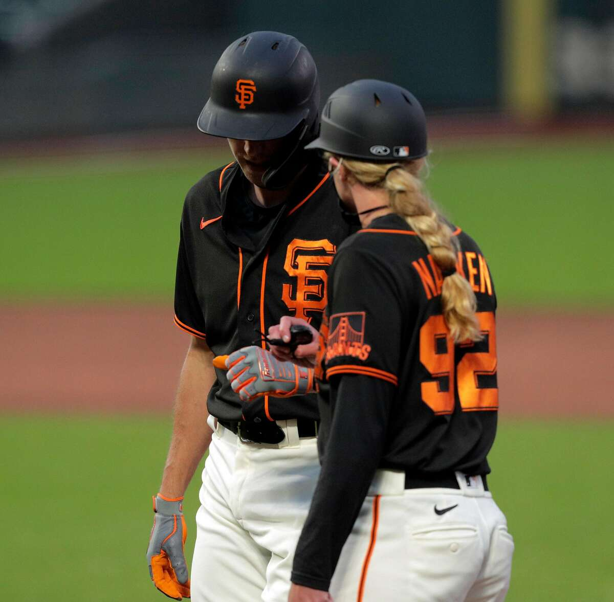 Hunter Pence (8) chats with Giants first base coach Alyssa Nakken after Pence singled in the first as the San Francisco Giants played the Oakland Athletics in a summer exhibition game at Oracle Park in San Francisco, Calif., on Tuesday, July 21, 2020.