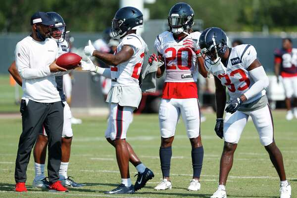 Houston Texans secondary coach D'Anton Lynn works with cornerback Gareon Conley (22), safety Justin Reid (20) and safety A.J. Moore Jr. (33) during an NFL training camp football practice Sunday, Aug. 23, 2020, in Houston.