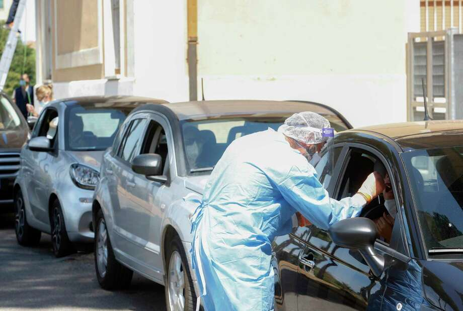 FILE - In this Aug. 17, 2020 file photo, a medical worker wearing protective gear collects a swab from a person sitting inside a car during Covid-19 tests at the the Santa Maria della Pieta' health center in Rome. Vacationers returning from Mediterranean Sea resorts abroad as well as on the Italian island of Sardinia have accounted for upward leaps in daily new case numbers. On Saturday, Italy registered 1,071 new cases, the highest daily number since mid-May, and only weeks after the nation had seen the number of day-to-day new infections plunge to about 200. (AP Photo/Riccardo De Luca) / Copyright 2020 The Associated Press. All rights reserved.