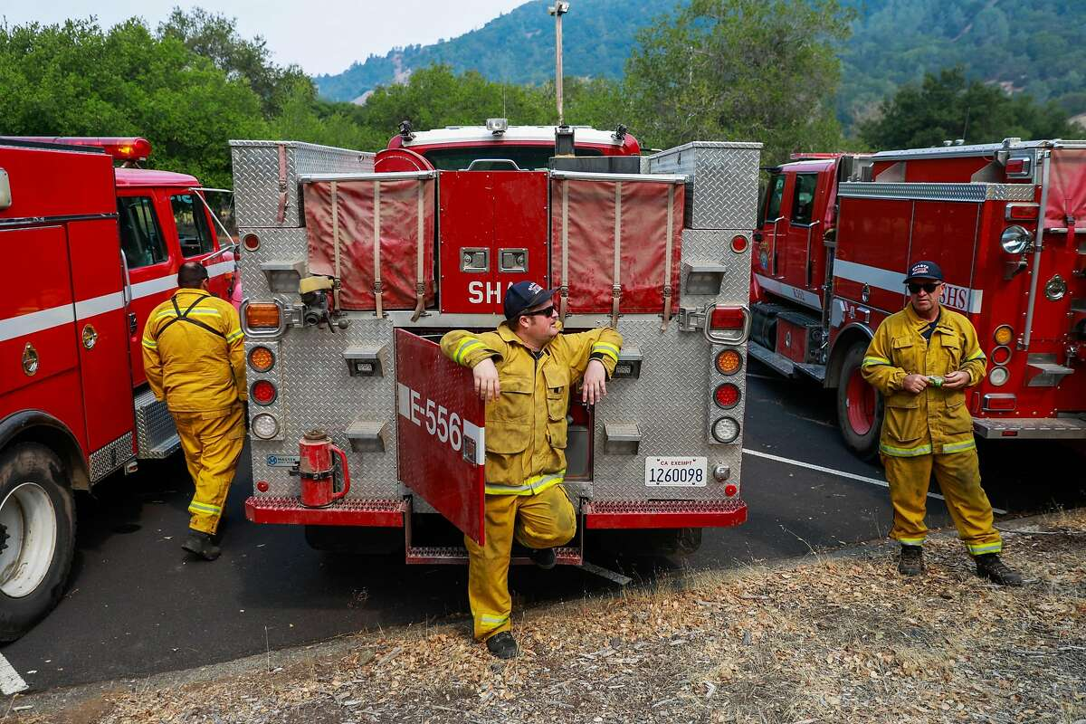 Firefighter Matt Kuska (center) waits to be assigned to an area at the LNU Lightning Complex Fire on Sunday, Aug. 23, 2020 in Geyserville, California.