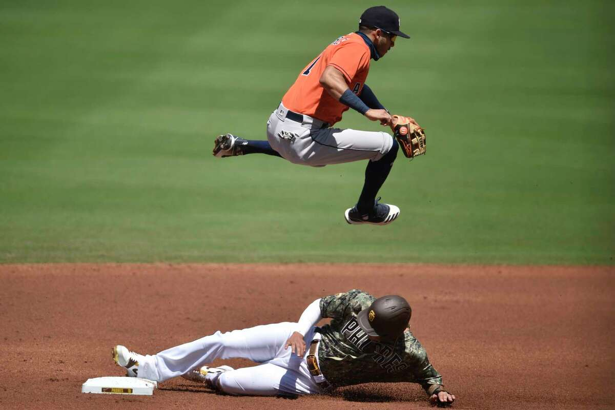 Houston Astros shortstop Carlos Correa, top, jumps to avoid San Diego Padres' Manny Machado as Machado steals second base off an errant throw during the first inning of a baseball game in San Diego, Sunday, Aug. 23, 2020. (AP Photo/Kelvin Kuo)