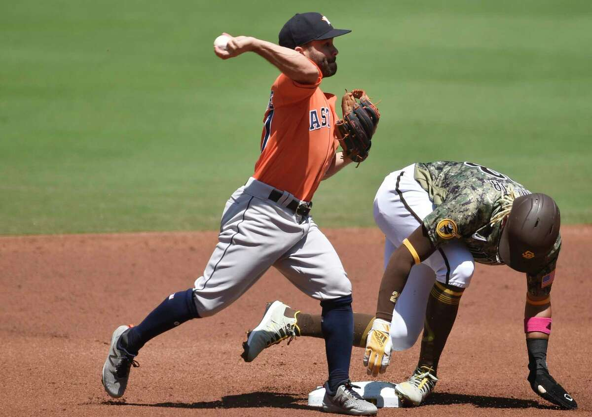 Houston Astros second baseman Jose Altuve, left, throws to first base after forcing out San Diego Padres' Fernando Tatis Jr. during the first inning of a baseball game in San Diego, Sunday, Aug. 23, 2020. Manny Machado was safe at first base. (AP Photo/Kelvin Kuo)