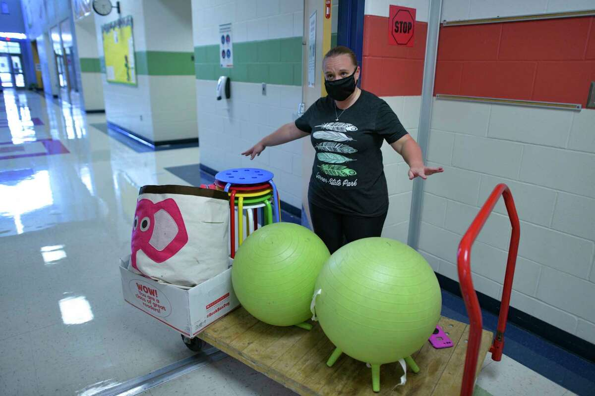 Erika Brendler, a third-grade teacher at Forester Elementary School, removes items that she acquired to benefit her students in past years to make space for social distancing in her classroom.