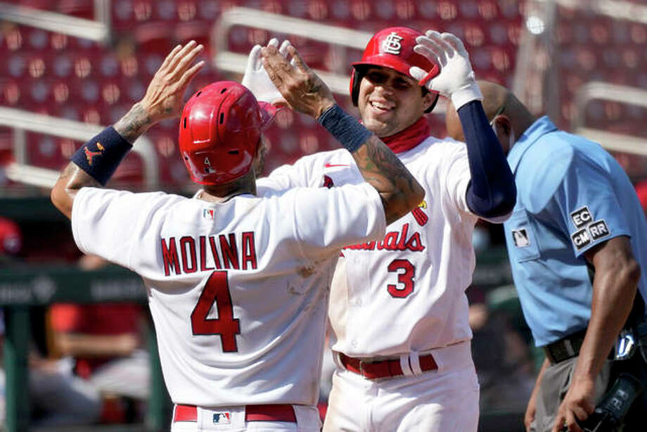 Cardinals rookie Dylan Carlson is congratulated by teammate Yadier Molina (4) after Carlson's two-run home run during the seventh inning against the Cincinnati Reds on Sunday at Busch Stadium. Photo: Associated Press