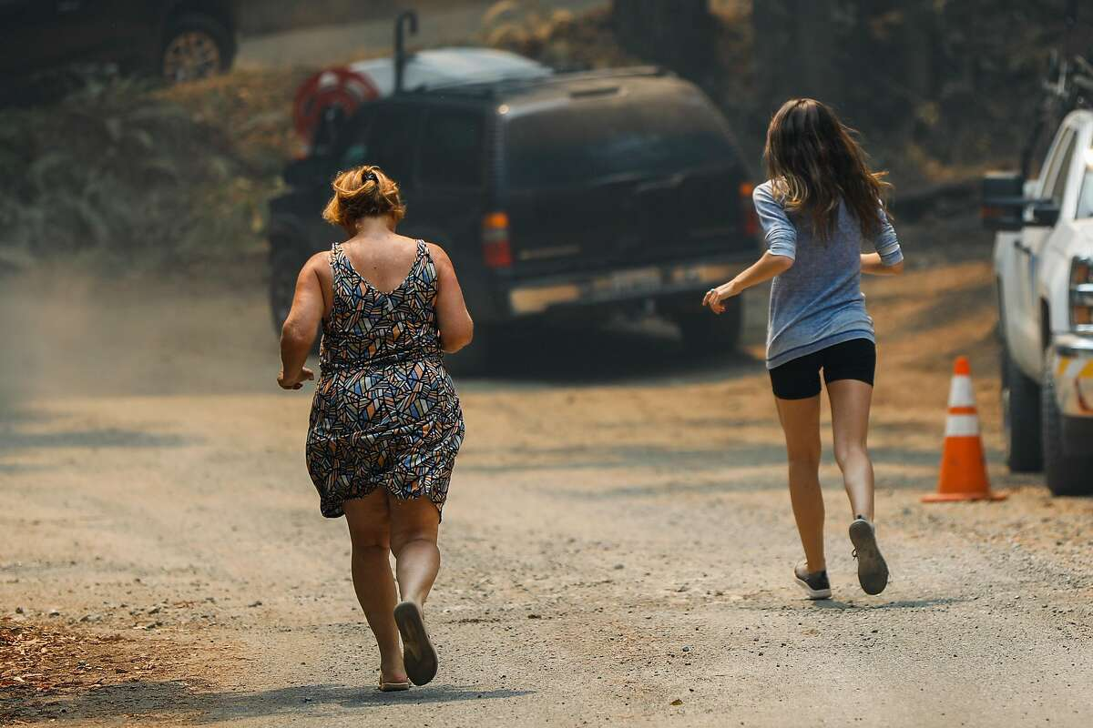 Milan Spadoni (right) and her boyfriend's mother Susan Cutino (left) run to get a news update after a spot fire sparked near their home during the LNU Lightning Complex Fire on Sunday, Aug. 23, 2020 in Healdsburg, California. The family has been fighting the fire on their own for the past four days with little sleep.