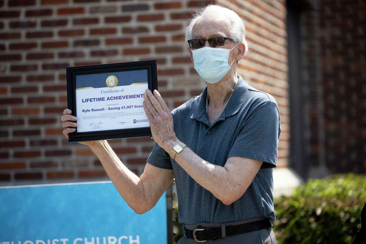 Kevin Russell holds the Lifetime Achievement award as he poses for portraits at The Woodlands United Methodist Church, Sunday, Aug. 23, 2020. Russell received the Lifetime Achievement award from the blood bank for his volunteer work since 1998.