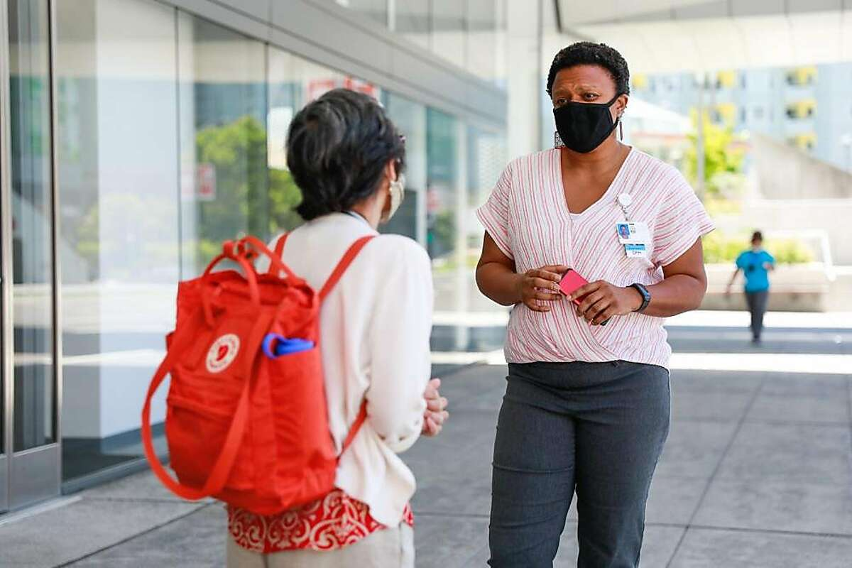 Ayanna Bennett (right) chats with a colleague outside the Moscone Center on Thursday, June 18, 2020 in San Francisco, California.