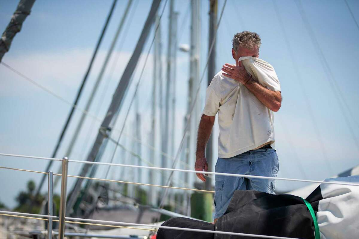 Laurence Wall wipes away sweat as he works to prepare his sailboat for a possible hurricane and its accompanying storm surge, Sunday, Aug. 23, 2020, at the Galveston Yacht Basin in Galveston.