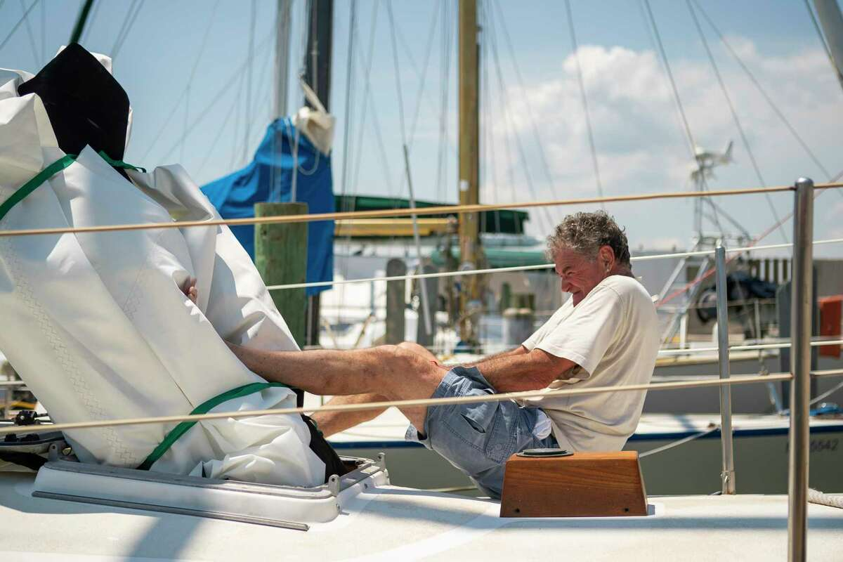 Laurence Wall stows away a sail as he prepares his sailboat for a possible hurricane and its accompanying storm surge, Sunday, Aug. 23, 2020, at the Galveston Yacht Basin in Galveston.