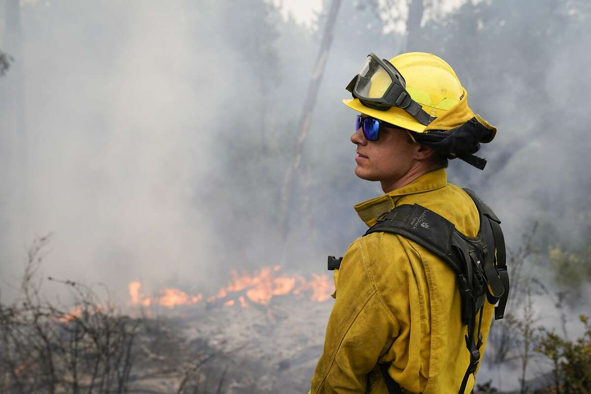 Firefighter Cody Nordstrom, of the North Central Fire station out of Kerman, Calif., monitors hot spots while fighting the CZU Lightning Complex Fire on Sunday, Aug. 23, 2020, in Bonny Doon, Calif. (AP Photo/Marcio Jose Sanchez)