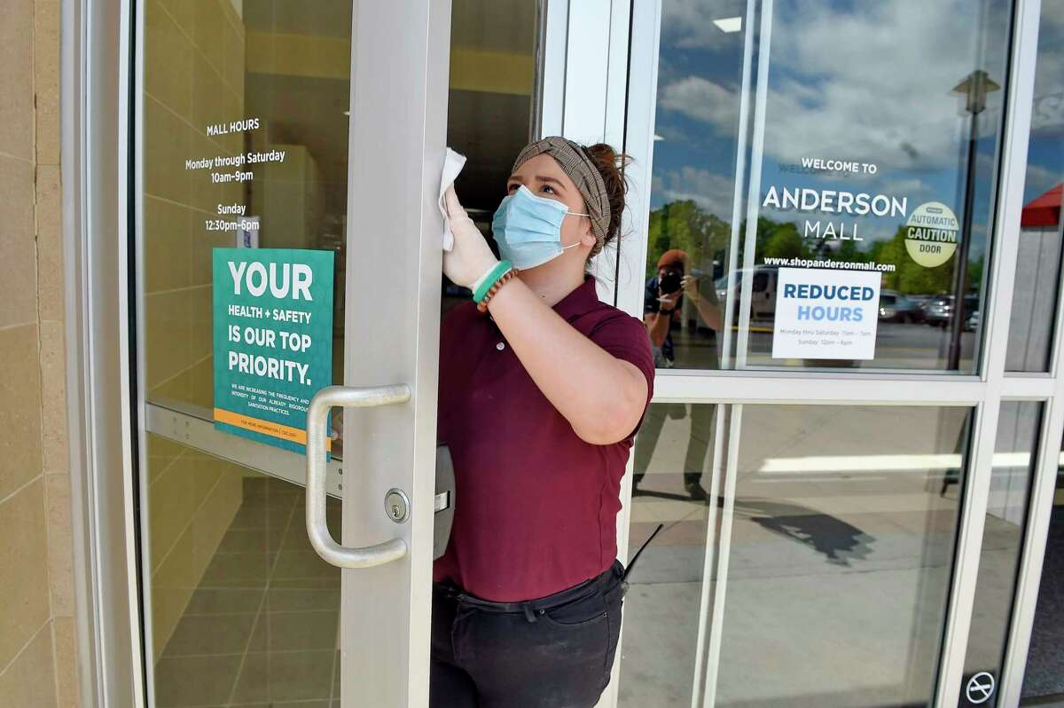 FILE - In this April 24, 2020, file photo, Kendall Ballew, an employee of the Anderson Mall, cleans the doors before the mall opened to limited business in Anderson, S.C. Records obtained by The Associated Press show governors working closely with business interests as they weighed when and how to reopen their economies during the coronavirus pandemic. (AP Photo/Richard Shiro, File)