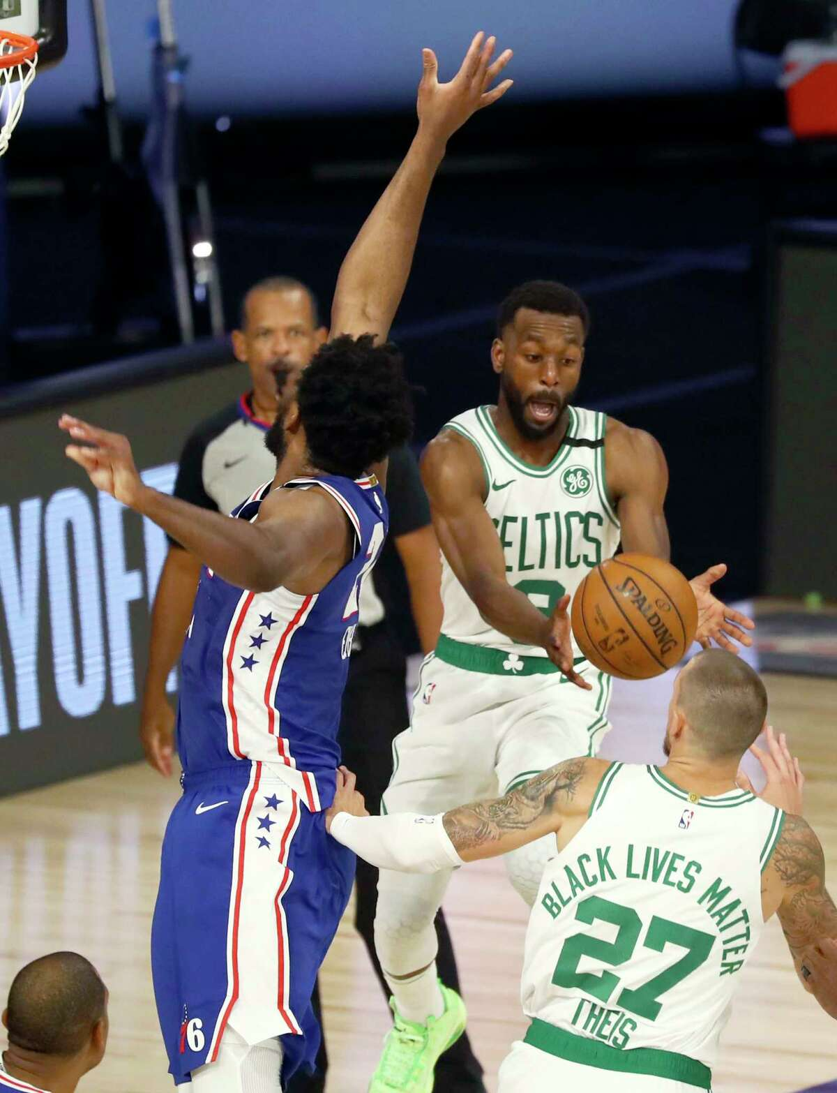 Boston Celtics guard Kemba Walker (8) passes the ball around Philadelphia 76ers center Joel Embiid, left, during the second quarter of Game 4 of an NBA basketball first-round playoff series, Sunday, Aug. 23, 2020, in Lake Buena Vista, Fla. (Kim Klement/Pool Photo via AP)
