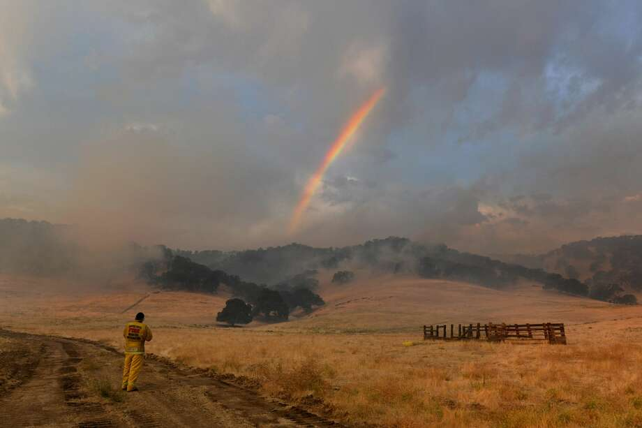 Retired Cal Fire captain Dan Dinneen, of Clayton, stops to take a picture of a rainbow as it appears above a grass fire burning on a hillside along Marsh Creek Road in Brentwood, Calif., on Monday, Aug. 17, 2020. Early Sunday morning a severe lightning storm caused several fires near the Round Valley Regional Preserve and Morgan Territory Regional Preserve. Last night residents in the area were asked to voluntary evacuate by local officials as the fire neared homes. (Photo by Jose Carlos Fajardo/MediaNews Group/East Bay Times via Getty Images) Photo: MediaNews Group/East Bay Times V/MediaNews Group Via Getty Images / Bay Area News Group - Digital First Media