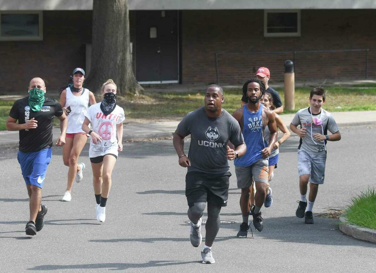 Justice for Brunch head of operations Tim Frazier leads the way as the #IRunWithMaud group makes its way past Eastern Middle School in Riverside on Sunday. Organized by Stamford civil rights group Justice for Brunch, the run was held in honor of Ahmaud Arbery, a Black man who was shot and killed by three white men while jogging near his home in Georgia. The 2.23 mile distance is symbolic of Feb 23, the date Arbery.