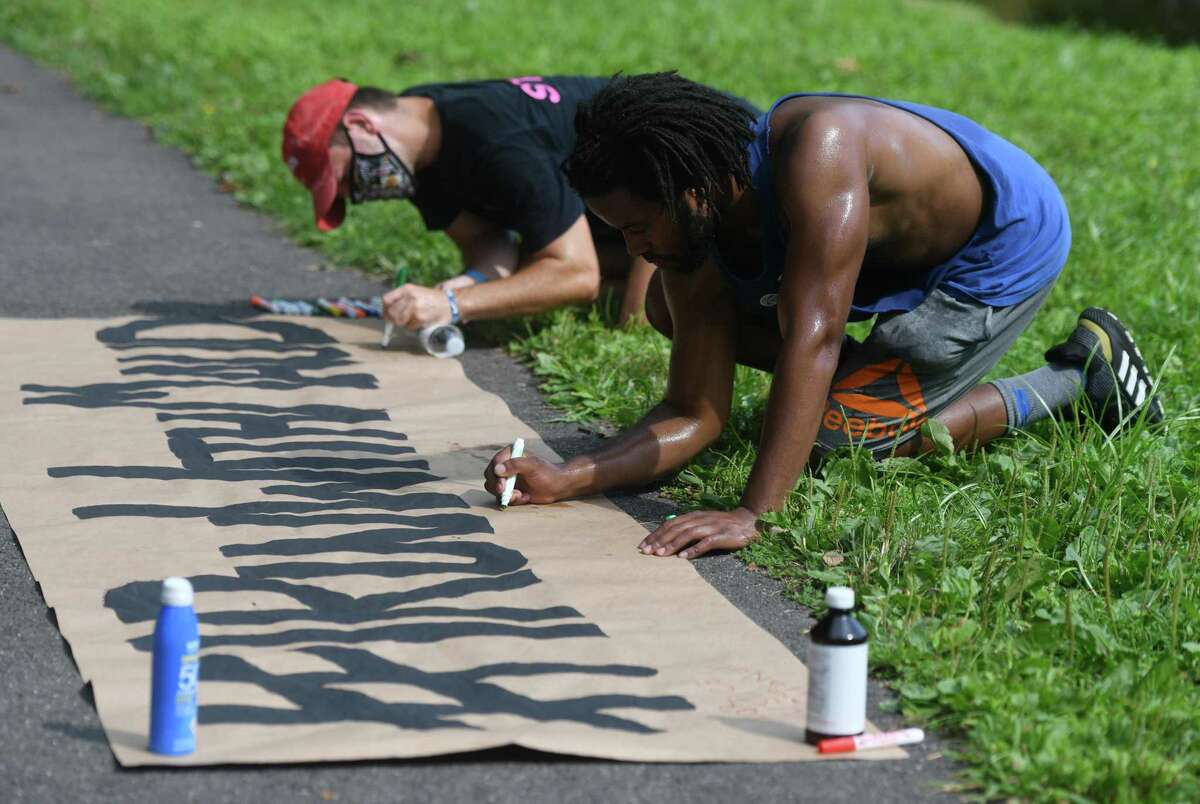 Bridgeport's Ray Swaby writes on the #IRunWithMaud banner after completing the 2.23 mile run at Binney Park in Old Greenwich, Conn. Sunday, Aug. 23, 2020. Organized by Stamford civil rights group Justice for Brunch, the run was held in honor of Ahmaud Arbery, a Black man who was shot and killed by three white men while jogging near his home in Georgia. The 2.23 mile distance is symbolic of the date that Arbery was killed, February 23, 2020.