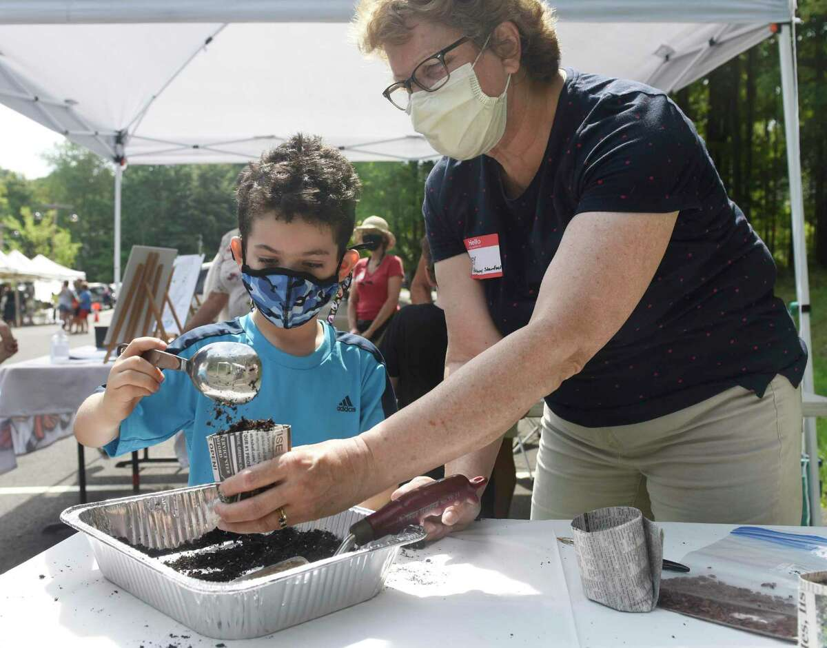 Michael Spira, 6, of New York, plants a native plant seed to take home with help from volunteer Peggy Erlenkotter at the Stamford Pollinator Pathway stand at the Stamford Museum & Nature Center Sunday Farm Market in Stamford, Conn. Sunday, Aug. 23, 2020. The pollinator pathway project aims to create a contiguous corridor of pollinator-friendly properties in Stamford to connect to adjoining regions in Greenwich and Darien that continue throughout the state and into New York. Right, Stamford's Abigail Smith, 4, plants a native plant seed for her to take home.
