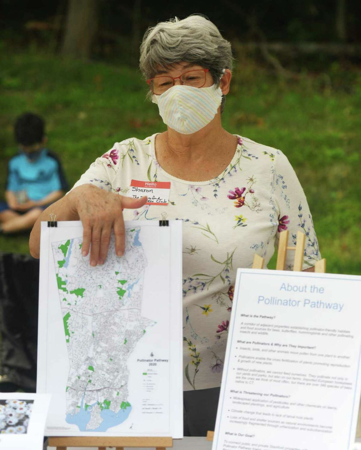 Sharon Larsen shows the map of connecting pollinator-friendly properties at the Stamford Pollinator Pathway stand at the Stamford Museum & Nature Center Sunday Farm Market in Stamford, Conn. Sunday, Aug. 23, 2020. The pollinator pathway project aims to create a contiguous corridor of pollinator-friendly properties in Stamford to connect to adjoining regions in Greenwich and Darien that continue throughout the state and into New York.