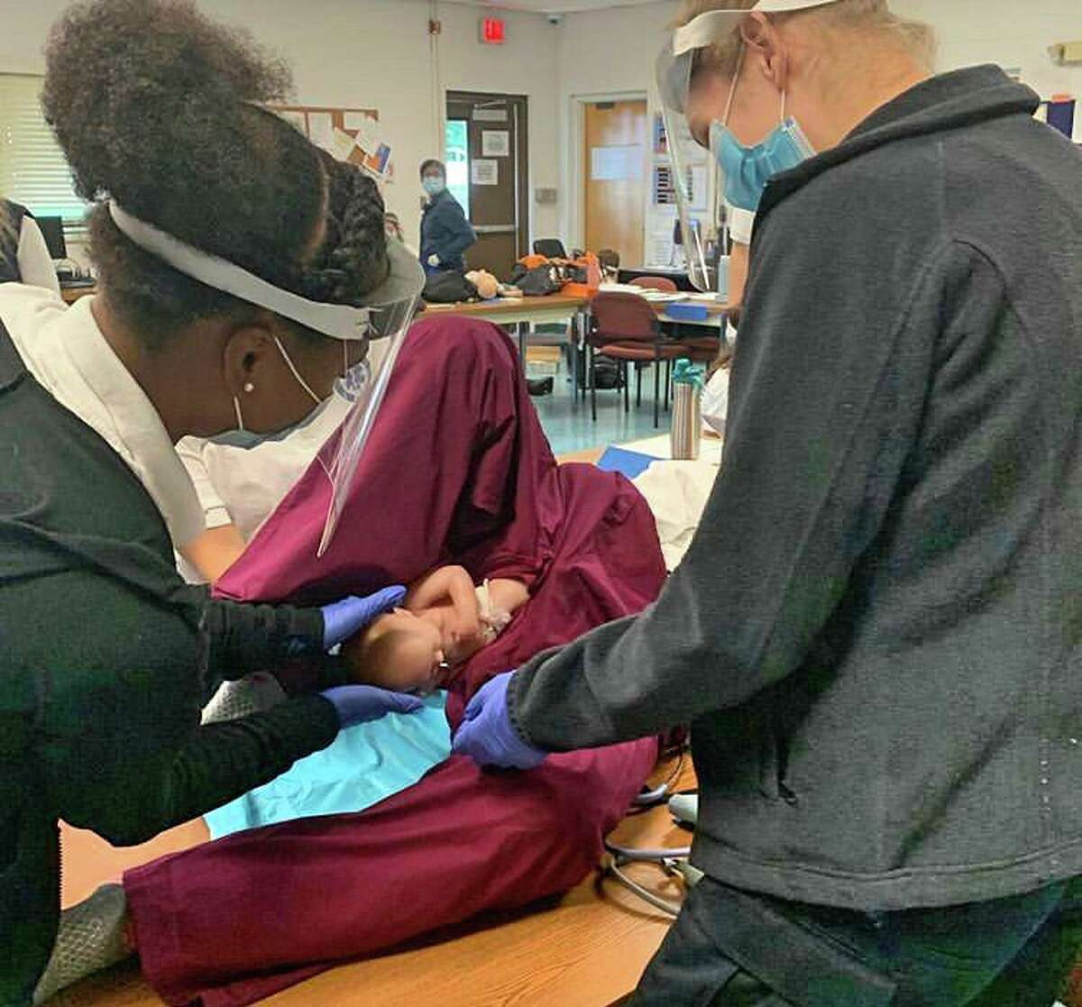 Students practice delivering a baby during the Trumbull EMT class.