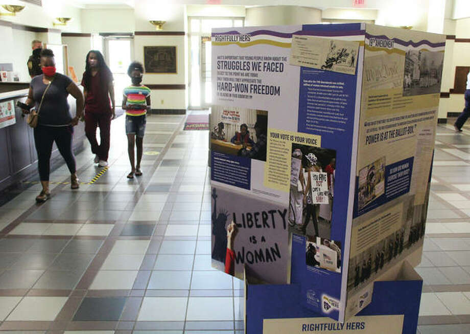 """Miranda Williams, of Madison, her niece and daugter pass by """"Rightfully Hers,"""" a """"pop-up"""" exhibit by the National Archives honoring the ratification of the 19th Amendment, which gave women the right to vote. The display went on display Tuesday in the Administration Building, 157 N. Main St., Edwardsville, and runs through Nov. 6. Ironically, Williams was in the building to register to vote."""