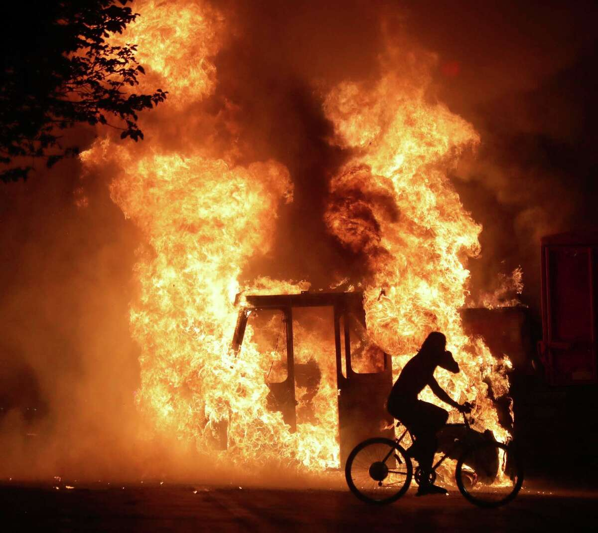 A man on a bike rides past a city truck on fire outside the Kenosha County Courthouse in Kenosha, Wis., on Sunday, Aug. 23, 2020. Kenosha police shot a man Sunday evening, setting off unrest in the city after a video appeared to show the officer firing several shots at close range into the man's back. (Mike De Sisti/Milwaukee Journal-Sentinel via AP)