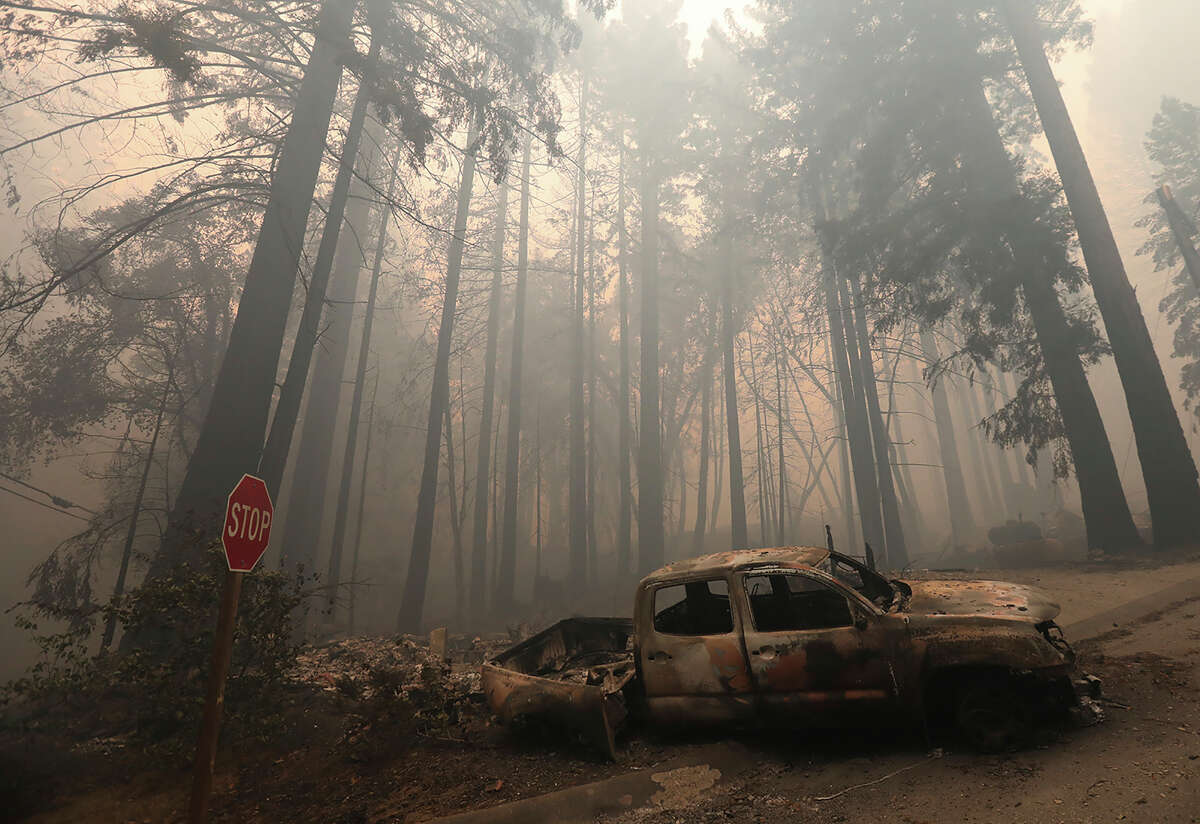 A burned-out vehicle is seen along Highway 236 in Boulder Creek, Calif., outside of Big Basin State Park, Friday, Aug. 21, 2020, where the CZU August Lightning Complex has grown.