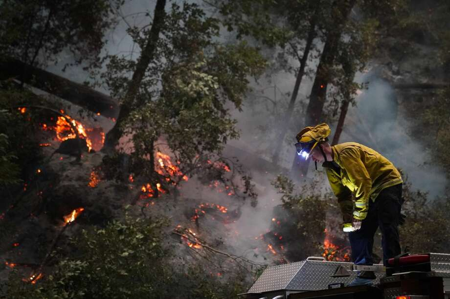 Ben Slaughter, a firefighter for the Boulder Creek Fire Department, stands on top of a fire truck along Highway 9 while monitoring flames from the CZU August Lightning Complex Fire, Saturday, Aug. 22, 2020, in Boulder Creek, Calif. Photo: Marcio Jose Sanchez/Associated Press / Copyright 2020 The Associated Press. All rights reserved.