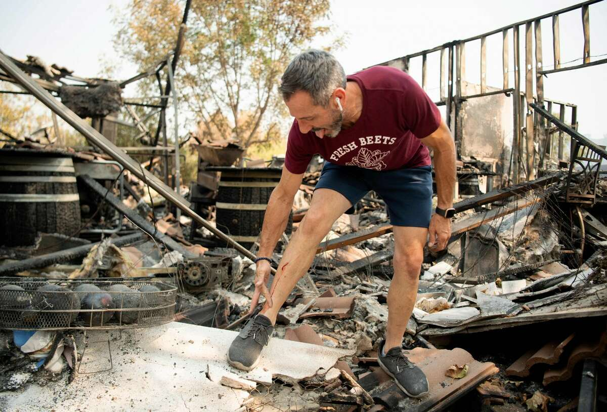 La Borgata Winery owner Gerry Iulano cuts his leg on charred remains at his winery during the LNU Lightning Complex fire in Vacaville, California on August 23, 2020.