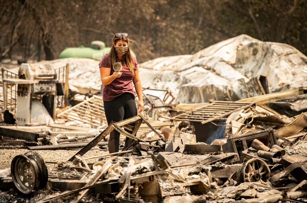 Resident Alyssa Medina reacts after finding an intact cup amidst the burned remains of her home during the LNU Lightning Complex fire in Vacaville, California on August 23, 2020.