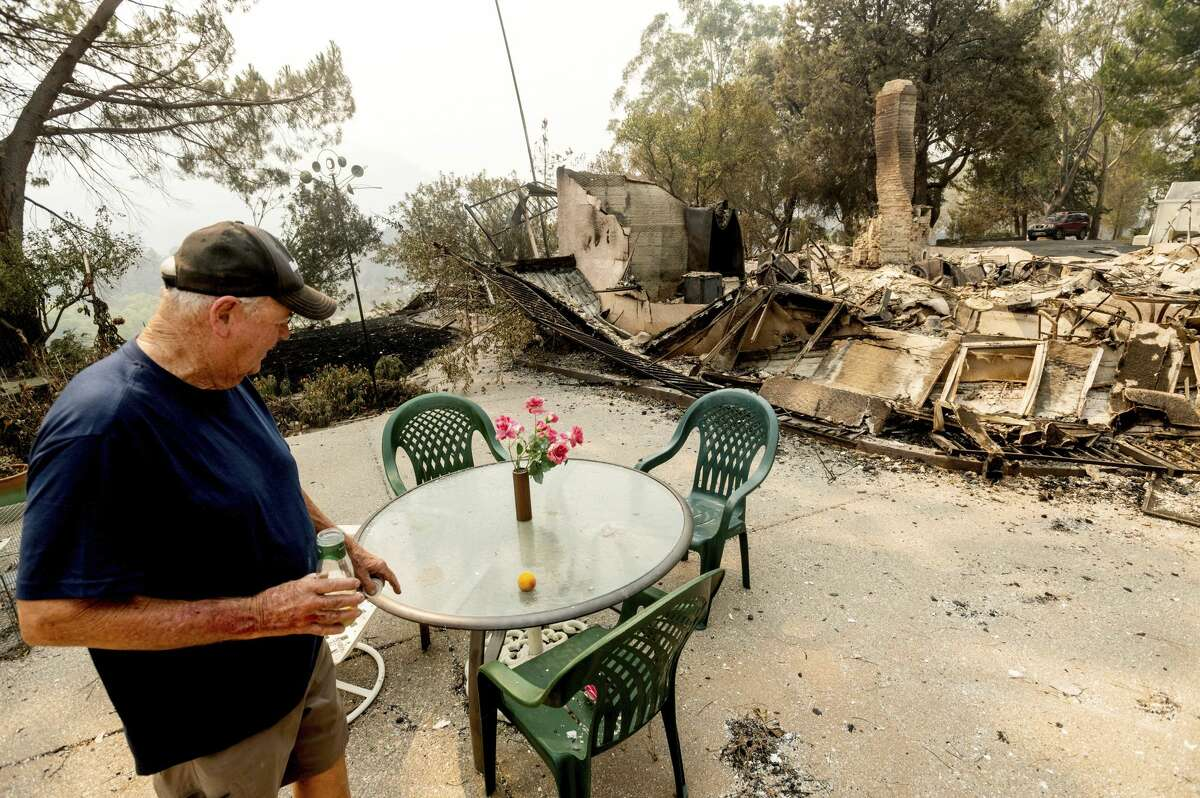 Hank Hanson, 81, looks at artificial flowers that remained standing as the LNU Lightning Complex fires destroyed his Vacaville, Calif., home on Friday, Aug. 21, 2020. Hanson, who built the house thirty years ago, does not think he will rebuild.
