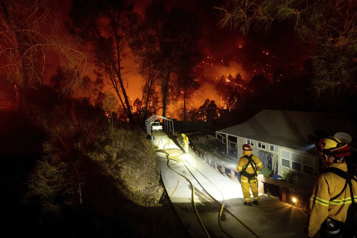 Firefighters protect a home in the Berryessa Estates neighborhood of unincorporated Napa County, Calif., as the LNU Lightning Complex fires burn on Friday, Aug. 21, 2020. The blaze forced thousands to flee and destroyed hundreds of homes and other structures