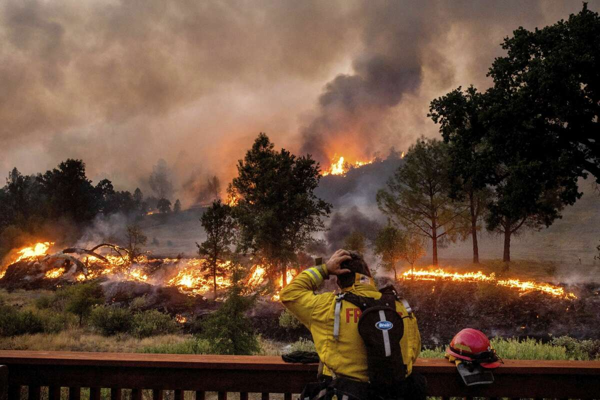 A firefighter rubs his head while watching the LNU Lightning Complex fires spread through the Berryessa Estates neighborhood of unincorporated Napa County. The blaze forced thousands to flee and destroyed hundreds of homes and other structures.