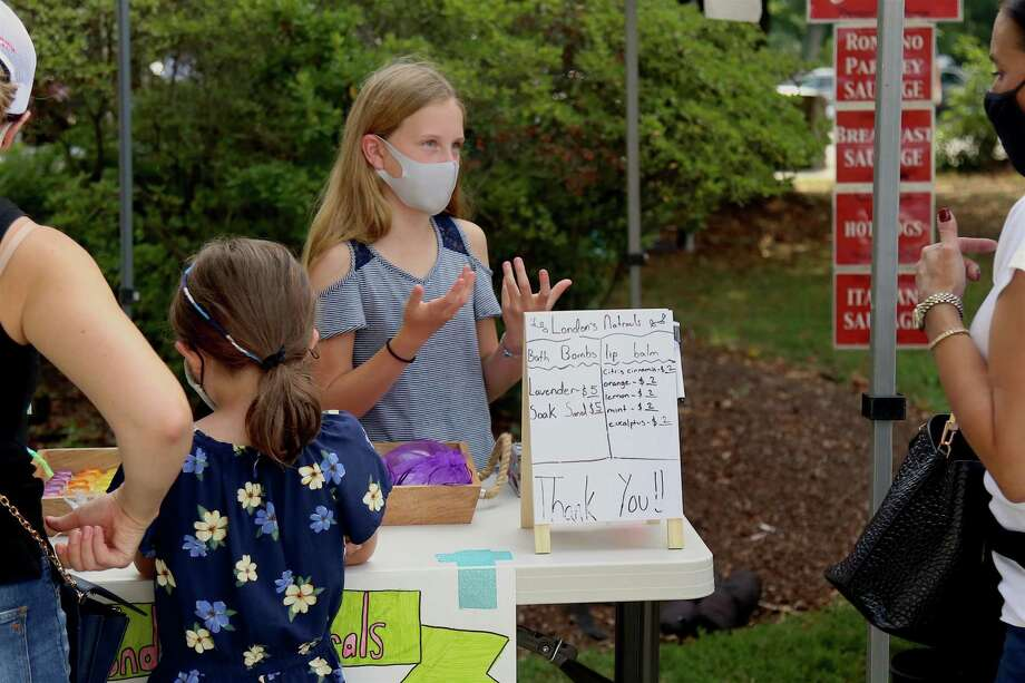 """London Elliott, 11, of Fairfield answers questions about her new business London's Naturals at the Fairfield Farmers Market on Sunday, Aug. 23, 2020, in Fairfield, Conn. For London Elliott, 11, of Fairfield, last weekend was the first time she unveiled her new company: London's Naturals, which features natural lip balms and bath bombs. Elliott said she wanted to follow in her father's footsteps and just launched the endeavor three weeks ago. """"I wanted to make my own business,"""" she said. """"You have to start somewhere, so I wanted to start here.""""  Photo: Jarret Liotta / Jarret Liotta / ©Jarret Liotta 2020"""
